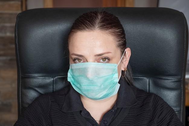 Retrato de una mujer en mascarilla médica en el trabajo