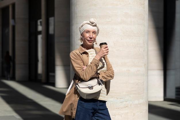Retrato de mujer mayor al aire libre en la ciudad con una taza de café