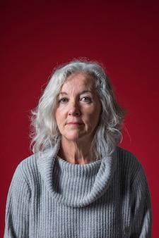 Retrato de una mujer mayor contra el telón de fondo rojo