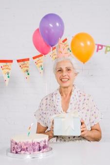 Retrato de una mujer mayor feliz que sostiene el regalo de cumpleaños con la torta en el escritorio