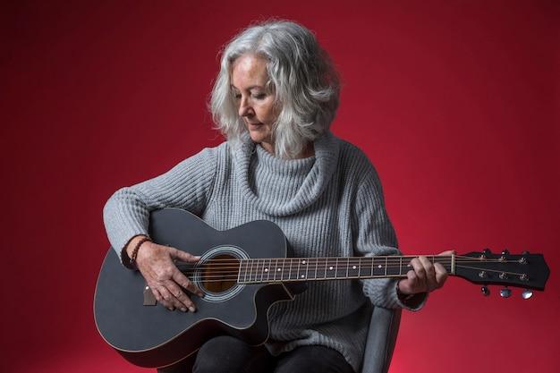 Retrato de una mujer mayor que se sienta en la silla que toca la guitarra contra fondo rojo
