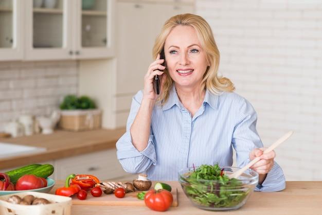 Retrato de una mujer mayor rubia sonriente que habla en el teléfono móvil que prepara la ensalada verde