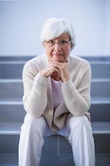 Retrato de mujer mayor sentada en las escaleras