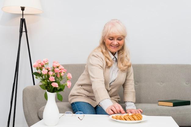 Retrato de una mujer mayor sentada en el sofá tomando galletas de la placa