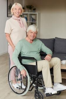 Retrato de mujer mayor sonriendo a la cámara mientras está de pie cerca de su marido discapacitado en silla de ruedas
