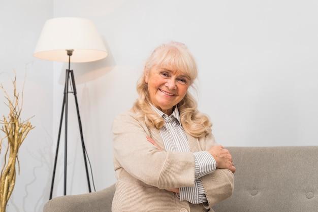Retrato de una mujer mayor sonriente que se coloca delante del sofá