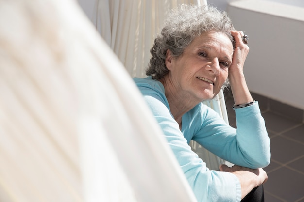 Retrato de la mujer mayor sonriente que miente en hamaca en balcón