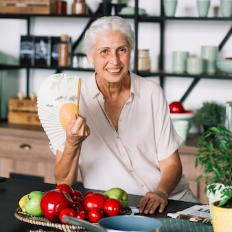 Retrato de la mujer mayor sonriente que se sienta delante de las frutas en la tabla
