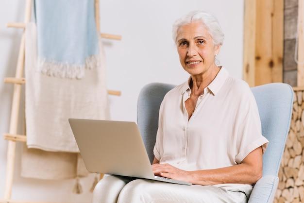 Retrato de la mujer mayor sonriente que se sienta en silla con el ordenador portátil que mira la cámara