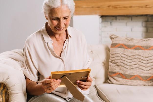 Retrato de la mujer mayor sonriente que se sienta en el sofá que mira el marco de la foto