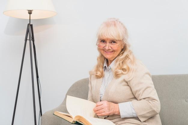 Retrato de una mujer mayor sonriente que se sienta en el sofá que sostiene el libro disponible