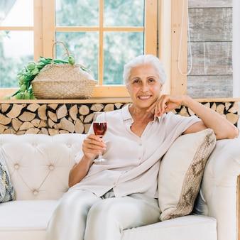 Retrato de la mujer mayor sonriente que se sienta en el sofá que sostiene el vidrio de vino