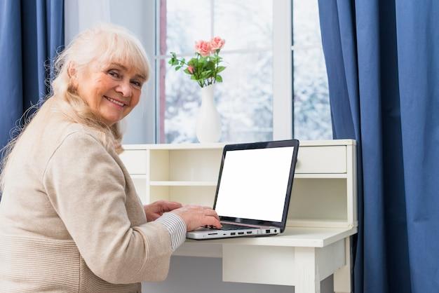 Retrato de una mujer mayor sonriente que usa el ordenador portátil con la pantalla blanca en blanco