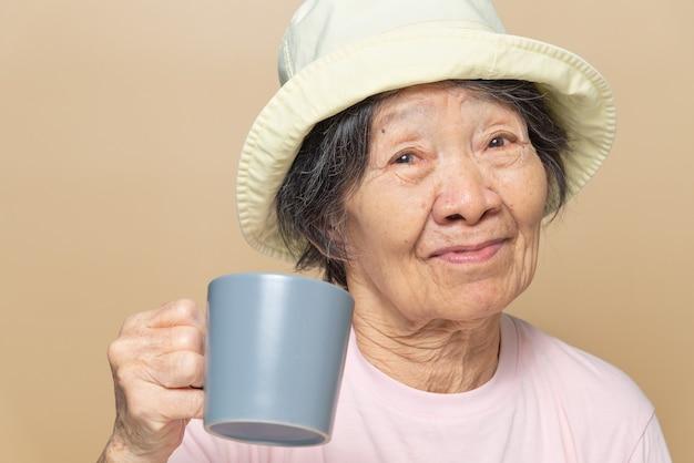 Retrato de mujer mayor del sudeste asiático sosteniendo una taza de café gris.