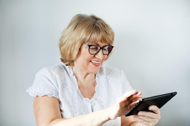 Retrato de una mujer mayor en vasos con una tableta sobre un fondo blanco.
