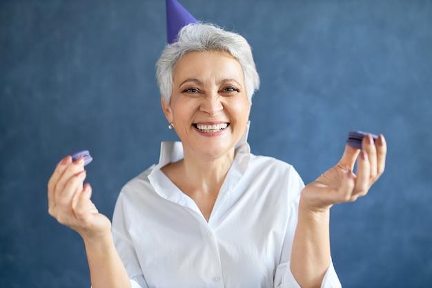 Retrato de mujer de mediana edad encantadora llena de alegría sonriendo ampliamente sosteniendo macarrones, disfrutando de un delicioso postre dulce en la fiesta de cumpleaños.
