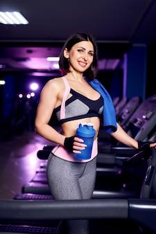 Retrato de una mujer de mediana edad saludable fitness sosteniendo agitador de botella de agua en el gimnasio