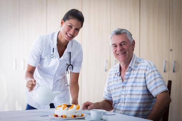 Retrato de mujer médico celebración seniors hombre cumpleaños en la sala de estar