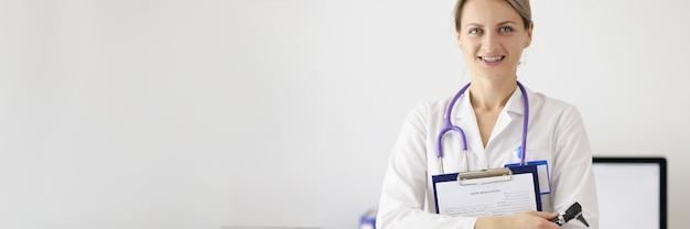 Retrato de mujer médico con documentos médicos y otoscopio en sus manos