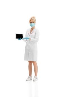 Retrato de mujer médico, enfermera o cosmetóloga en uniforme blanco y guantes azules sobre blanco. Foto gratis