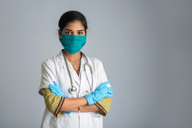 Retrato de mujer médico con una máscara protectora y guantes con un estetoscopio. epidemia mundial del concepto de coronavirus.