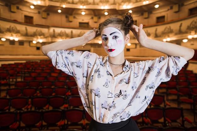 Retrato de mujer mimo de pie en un auditorio