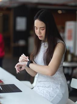 Retrato de mujer mirando smartwatch mientras trabaja en el espacio de trabajo co