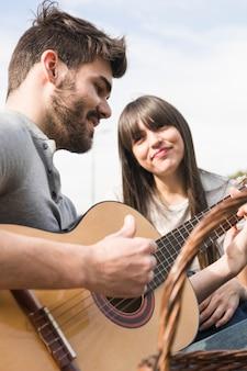Retrato de mujer mirando a su novio tocando la guitarra