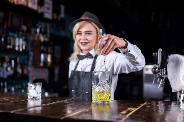 Retrato de mujer mixóloga está vertiendo una bebida en el club nocturno