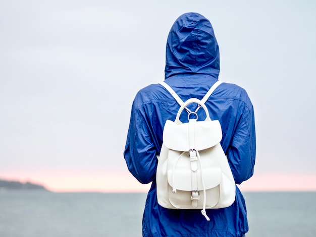 Retrato mujer con mochila en la orilla del mar