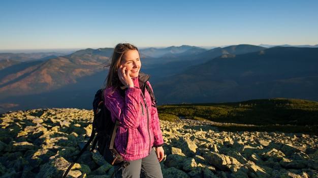 Retrato de mujer mochilero de pie en la cima de la montaña