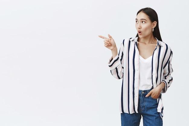 Retrato de mujer de moda despreocupada asombrada en blusa a rayas y jeans, sosteniendo la mano en el bolsillo, mirando y apuntando a la izquierda con asombro e interés, discutiendo cosas intrigantes