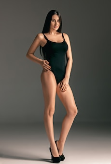Retrato de mujer de moda. hermosa modelo adolescente en traje de baño negro.