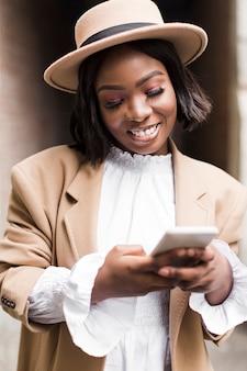 Retrato de mujer de moda sonriente mirando su teléfono