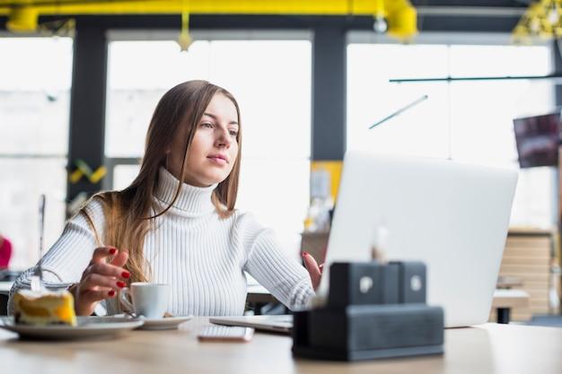 Retrato de mujer moderna trabajando con portátil