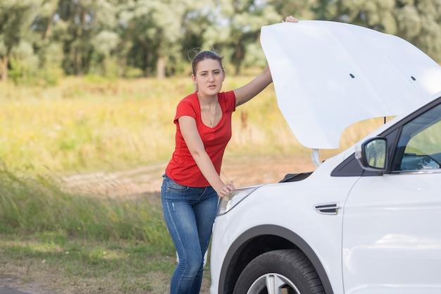 Retrato de mujer molesta de pie en el coche roto en el borde de la carretera