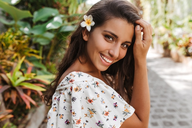 Retrato de mujer morena en blusa con estampado floral con flor blanca en el pelo
