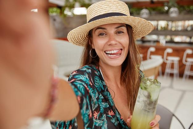 Retrato de mujer morena divertida lleva sombrero de paja, posa para selfie, muestra lengua, bebe cóctel refrescante, se alza contra el interior del café. hermosa joven modelo disfruta de las vacaciones de verano