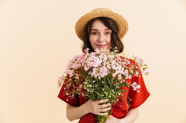 Retrato de mujer morena encantadora con sombrero de paja sonriendo y sosteniendo ramo de flores aislado