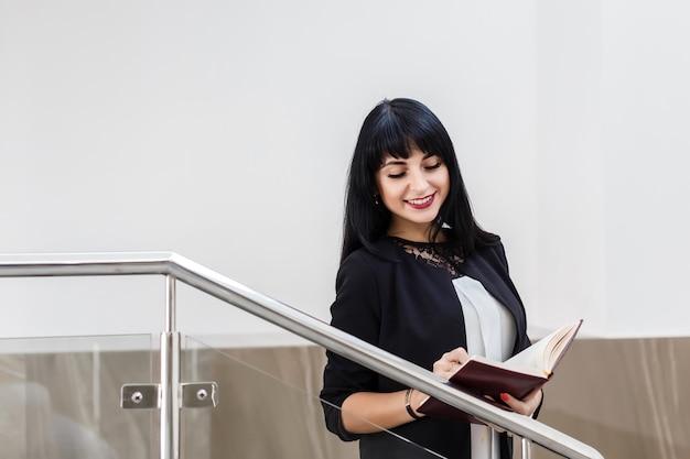 El retrato de la mujer morena feliz hermosa joven se vistió en un traje de negocios negro que trabajaba con un cuaderno, colocándose en la oficina, sonriendo.