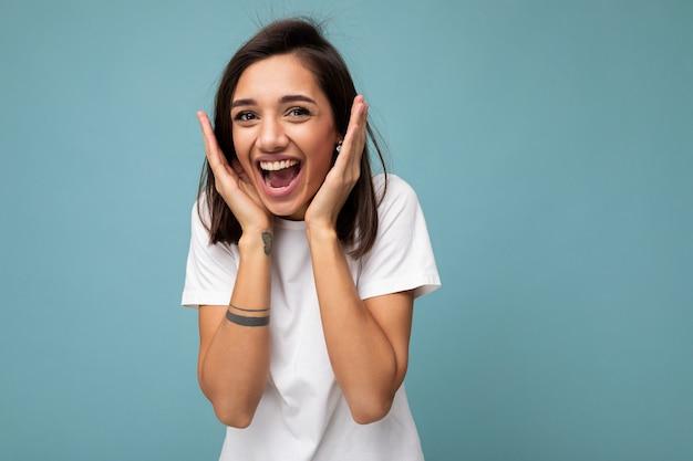 Retrato de mujer morena hermosa joven encantadora sonriente positiva feliz con emociones sinceras vistiendo camiseta blanca casual para maqueta aislada en superficie azul con espacio de copia