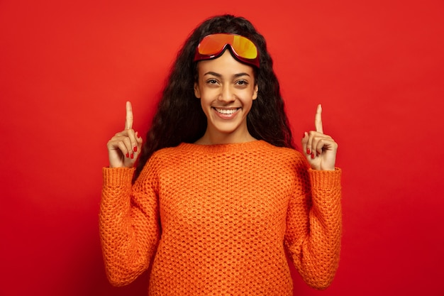 Retrato de mujer morena joven afroamericana en pasamontañas en espacio rojo