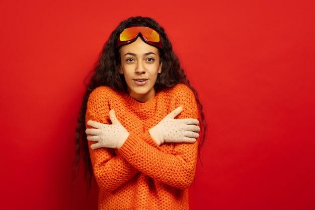 Retrato de mujer morena joven afroamericana en pasamontañas en rojo