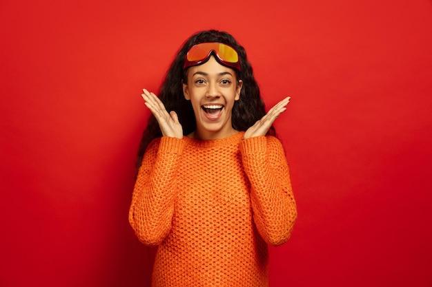 Retrato de mujer morena joven afroamericana en pasamontañas sobre fondo rojo de estudio. concepto de emociones humanas, expresión facial, ventas, publicidad, deportes de invierno y vacaciones. sorprendido, asombrado.