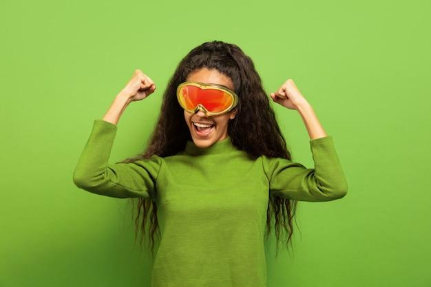 Retrato de mujer morena joven afroamericana en pasamontañas sobre fondo verde de estudio. concepto de emociones humanas, expresión facial, ventas, publicidad, deportes de invierno y vacaciones. sonriendo, celebrando.