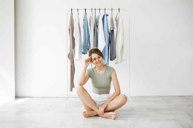 Retrato de la mujer morena joven alegre que sonríe sentado en piso sobre el armario de la suspensión y la pared blanca.