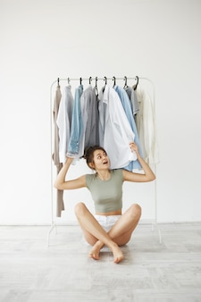 Retrato de la mujer morena joven alegre que sonríe sentarse en piso entre la ropa en el armario de la suspensión sobre la pared blanca.