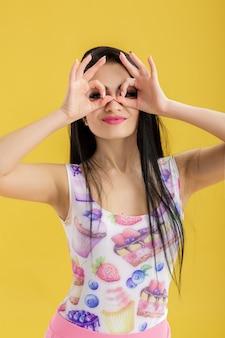 Retrato de mujer morena joven atractiva en camiseta rosa sin mangas en amarillo gracioso mujer con cabello oscuro