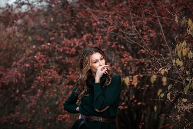 El retrato de la mujer morena joven atractiva con el pelo fijó en suéter verde del otoño y la falda larga que presentaba en el parque del otoño. copia espacio