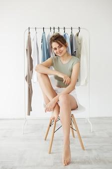Retrato de la mujer morena joven que sonríe sentado en silla sobre el armario de la suspensión y la pared blanca.